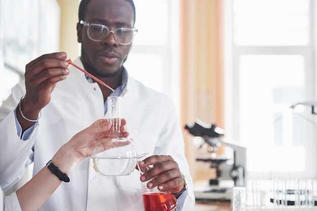 Een afro-amerikaanse werknemer werkt in een laboratorium en voert experimenten uit.
