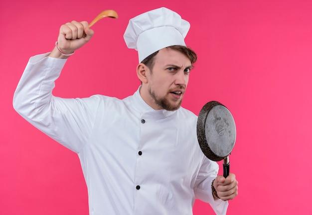 Een agressieve jonge, bebaarde chef-kokmens in wit uniform die houten lepel met koekenpan houdt terwijl hij op een roze muur kijkt