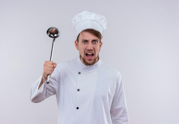 Een agressieve jonge, bebaarde chef-kokmens in wit uniform houdt pollepel terwijl hij op een witte muur kijkt