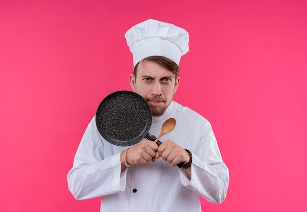 Een agressieve jonge, bebaarde chef-kokmens in wit uniform toont x-teken met koekenpan en houten lepel terwijl hij op een roze muur kijkt