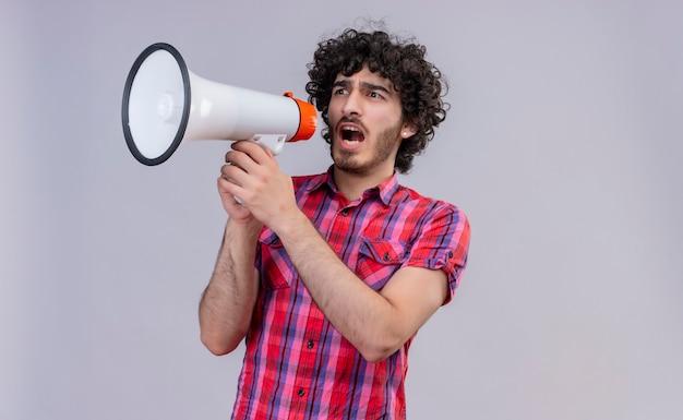 Een agressieve jonge knappe man met krullend haar in een geruit overhemd met een megafoon en iets wil zeggen
