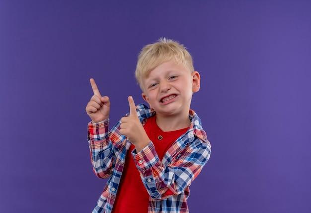 Een agressieve schattige kleine jongen met blond haar, gekleed in een geruit overhemd dat met wijsvingers omhoog wijst