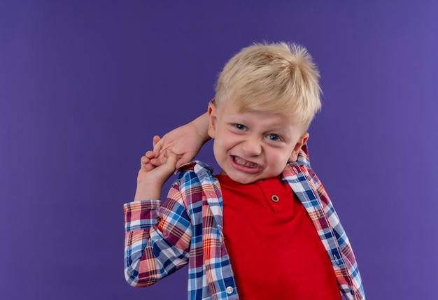 Een agressieve schattige kleine jongen met blond haar, gekleed in geruit overhemd kijken