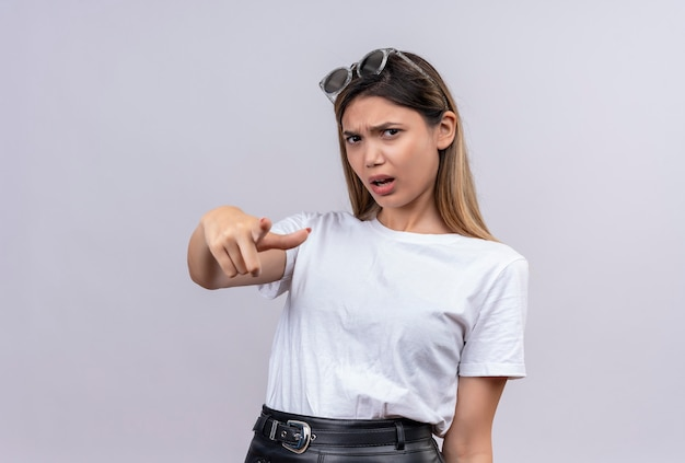 Een agressieve vrij jonge vrouw in wit t-shirt die zonnebril op haar hoofd draagt die naar voorzijde met wijsvinger richt