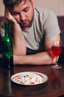 Een alcoholverslaafde man is aan een tafel in slaap gevallen