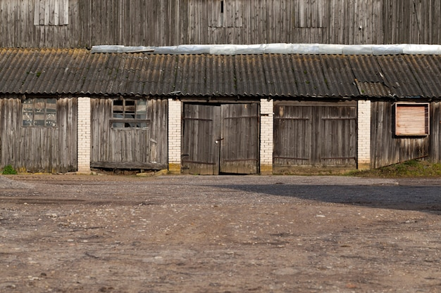 Een algemeen overzicht van een oud verlaten gebouw met gesloten poorten gemaakt van houten planken