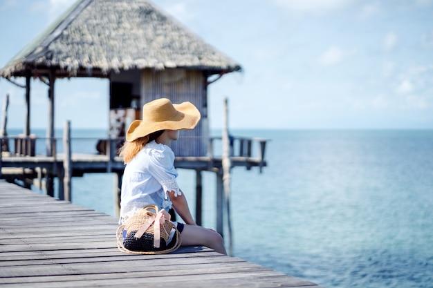 Een alleenstaande vrouw zittend op de houten brug - koh mark, thailand