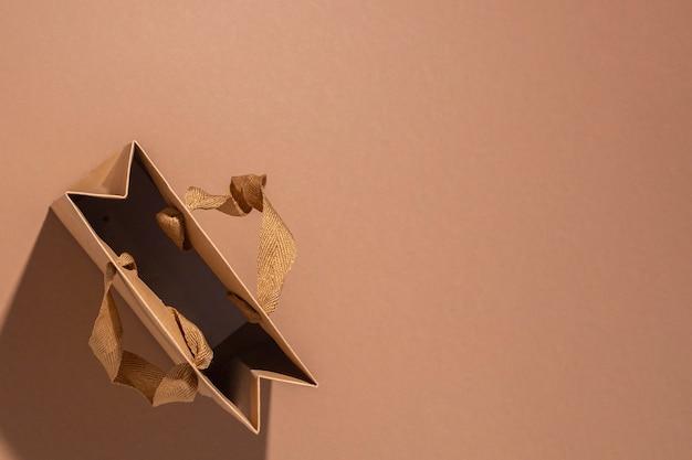 Een ambachtelijke cadeautas met satijnen lint op bruine achtergrond. bovenaanzicht, plat gelegd.