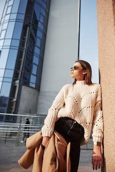 Een andere persoon loopt achter. mooi meisje in warme kleren lopen in het weekend in de stad