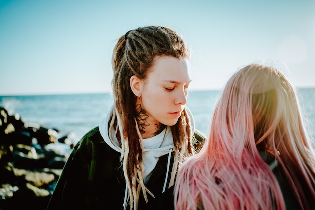 Een androgyn meisje met dreadlocks en een tatoeage in haar nek kijkt naar een meisje met roze haar dat achter haar aan de kust staat