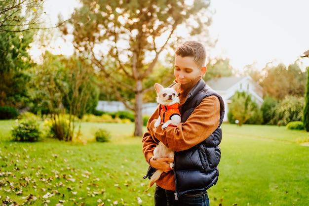 Een androgyn meisje met een kort kapsel houdt een chihuahuahond vast in een oranje vest. hoge kwaliteit foto