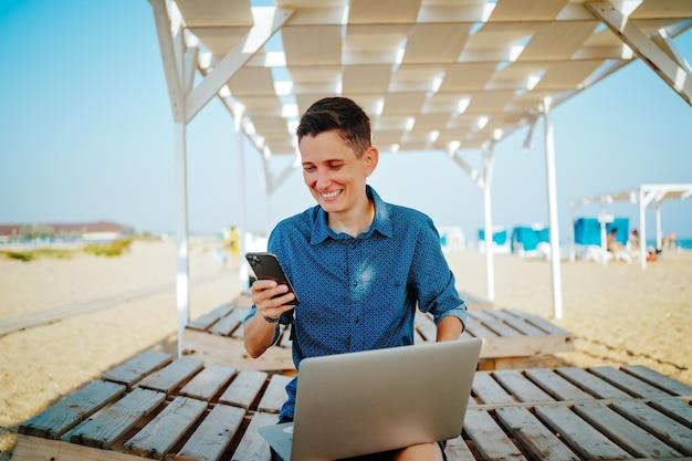 Een androgyne vrouw met kort rood haar en een horloge op haar hand lacht en houdt een telefoon en laptop vast op een zandstrand. hoge kwaliteit foto