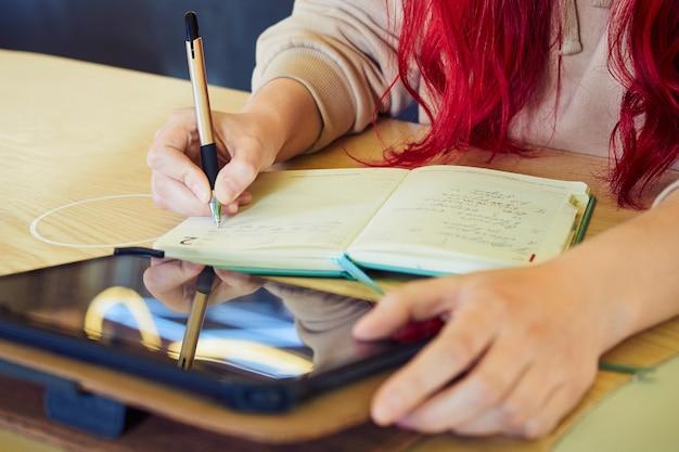 Een anonieme afbeelding van een vrouw die op afstand werkt in een café met een tablet, schrijft in een dagboek.