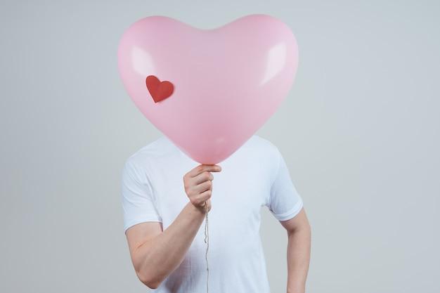 Een anonieme man in een wit t-shirt met een hartvormige ballon. fijne valentijnsdag.