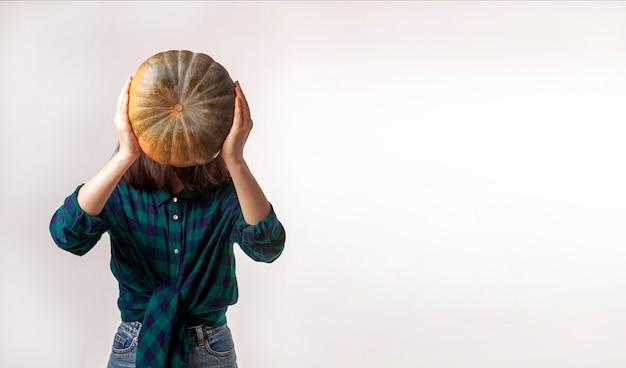 Een anonieme vrouw houdt een pompoen vast
