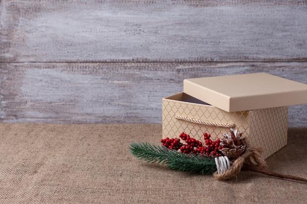 Een ansichtkaart uit een beige geschenkdoos met een open deksel en een takje van een kerstboom