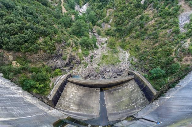 Een antenne brede hoekmening van de muur van een dam vlak vóór de bomen & gebladerte in amer, spanje