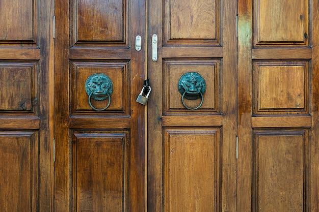 Een antiek metalen handvat met een leeuw op een oude bruine houten deur