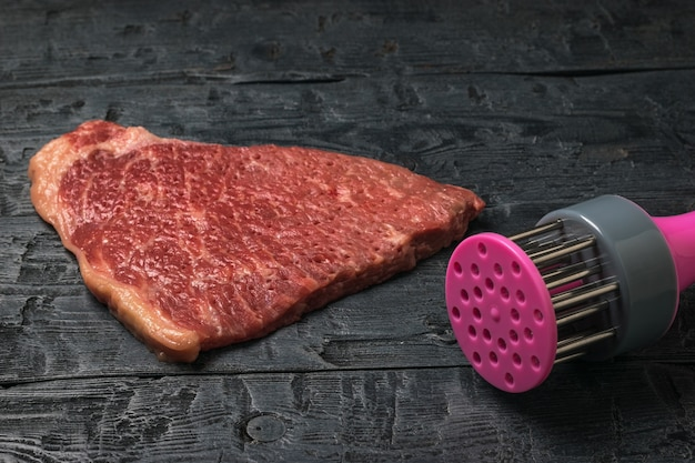 Een apparaat voor het koken van karbonades en een stuk rundvlees op een houten tafel. vleesgerechten koken.