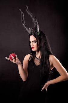 Een appel in de handen van een gehoornde heks