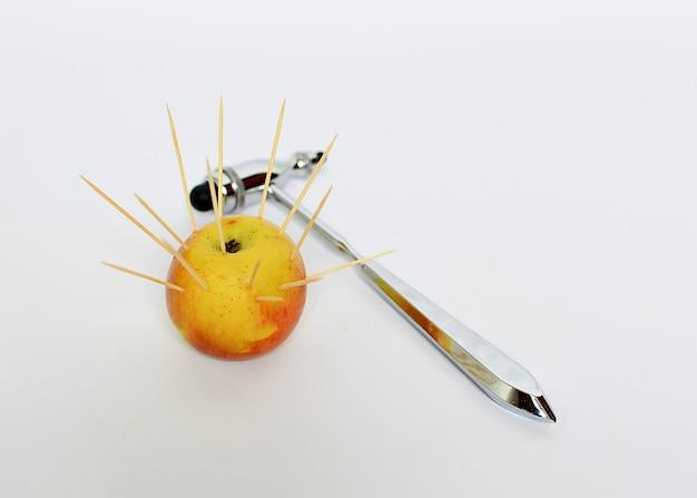 Een appel waarin scherpe tandenstokers uitsteken en een neurologische hamer op een witte achtergrond.