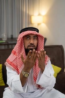 Een arabische jongeman bidt tot allah met zijn handen omhoog