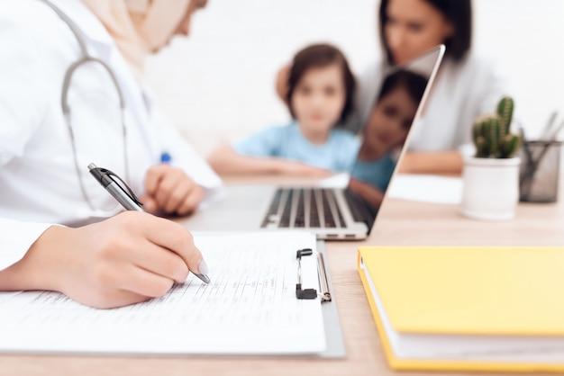 Een arabische vrouw arts schrijft een diagnose van een zieke jongen.