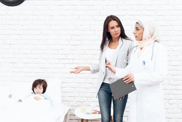 Een arabische vrouwelijke arts communiceert met de moeder.