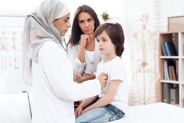 Een arabische vrouwelijke arts onderzoekt een zieke jongen.