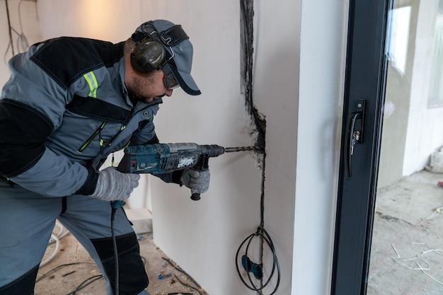 Een arbeider boort een gat in de muur met een perforator voor draden