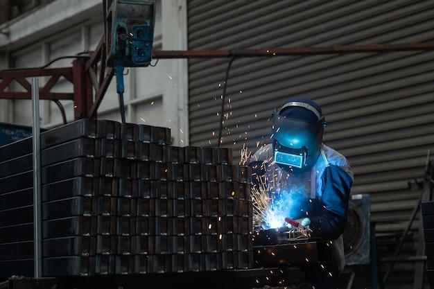 Een arbeider die staal lassen, veiligheid op baan