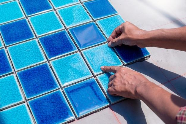 Een arbeider die tegels thuis zet herstelt, installatie van tegels op de lijm
