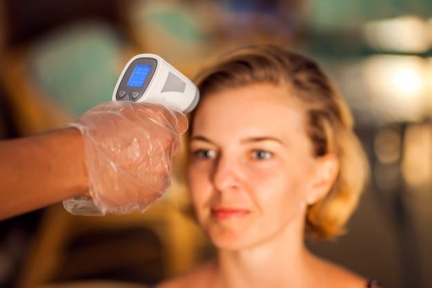 Een arbeider die temperatuur van vrouwenbezoeker binnenkant van het koffiehuis meet. leven tijdens coronavirustijd