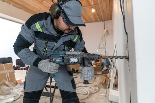Een arbeider, gekleed in een overall, een bril en een speciale koptelefoon voor geluidsreductie, boort een gat in de muur voor draden