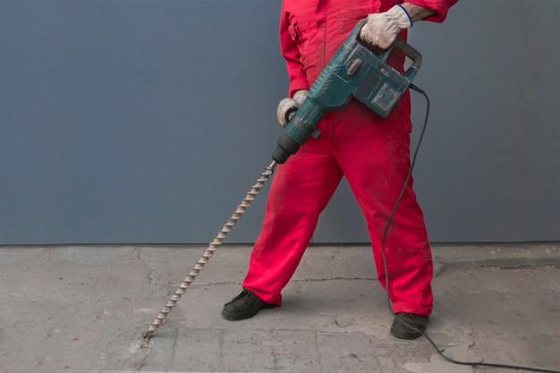 Een arbeider in een overall die met een boor met een lange boor werkt, vernietigt de betonnen vloer