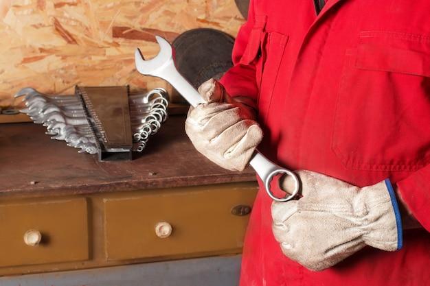 Een arbeider in een rode overall houdt een moersleutel vast in leren beschermende handschoenen in een werkplaats