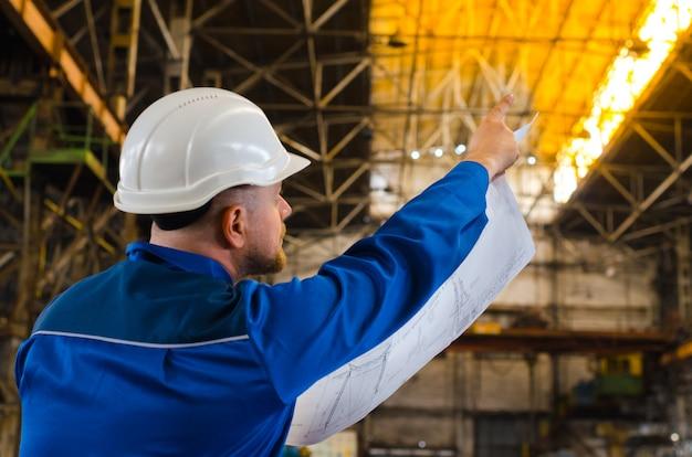 Een arbeider in overall en een witte helm onderzoekt de tekening en wijst met zijn wijsvinger