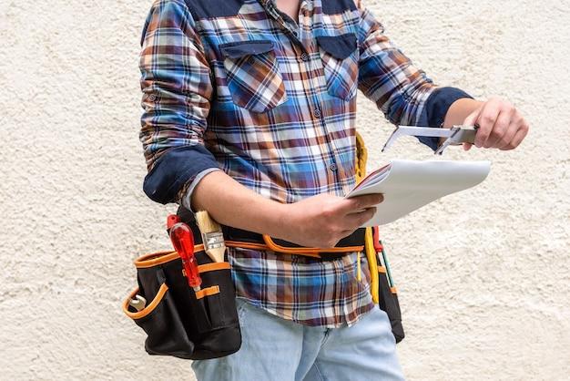 Een arbeider met gereedschap in zijn riem houdt documenten en een meetinstrument vast.