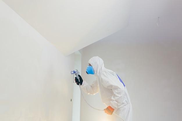 Een arbeider schildert de muren met een spuitpistool in een nieuw gebouw