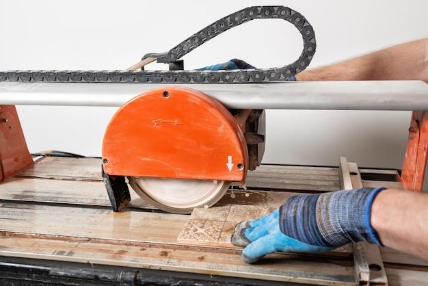 Een arbeider snijdt een keramische tegel op een natte zaagmachine