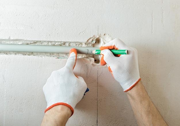 Een arbeider snijdt het deel van de isolatie af met een snijder