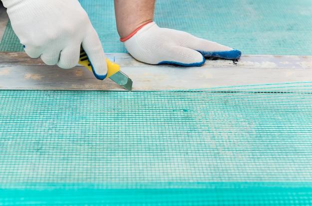 Een arbeider snijdt met een mes een stuk glasvezelgaas af.