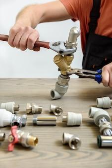 Een arbeider verbindt elementen van het sanitair.