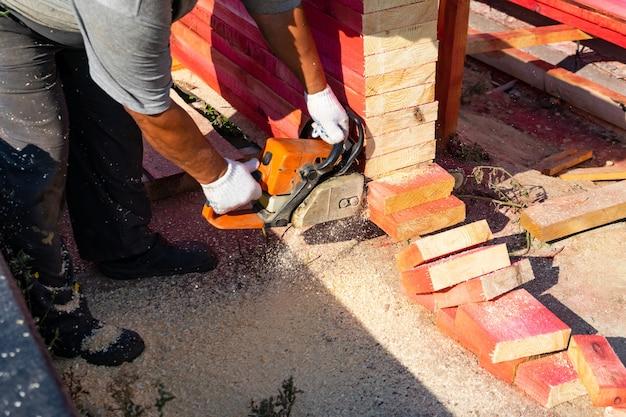 Een arbeider zaagt een houten plank van een kettingzaag af. woningbouw.