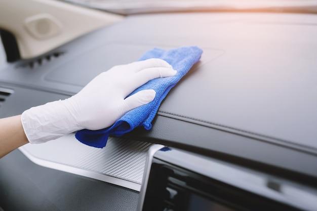 Een arbeidershand draagt ?? handschoen die het stuurwiel van de autoconsole schoonmaakt met microvezeldoek, autowasserette detaillering concept.