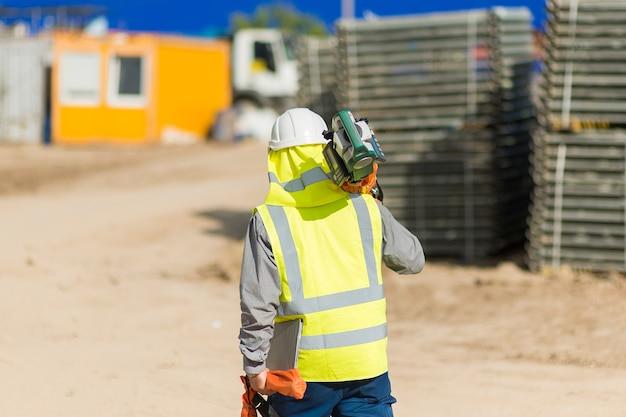 Een architect met een laserwaterpas loopt door het bouwgebied