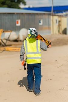 Een architect met een laserwaterpas loopt langs de bouwplaats, zicht van achteren