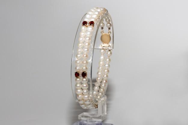 Een armband gemaakt van parels, granaat en diamanten met een gouden sluiting. geel goud en edelstenen