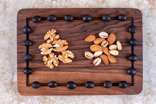 Een arrangement van chocoladesuikergoed en notenstapels op een bord