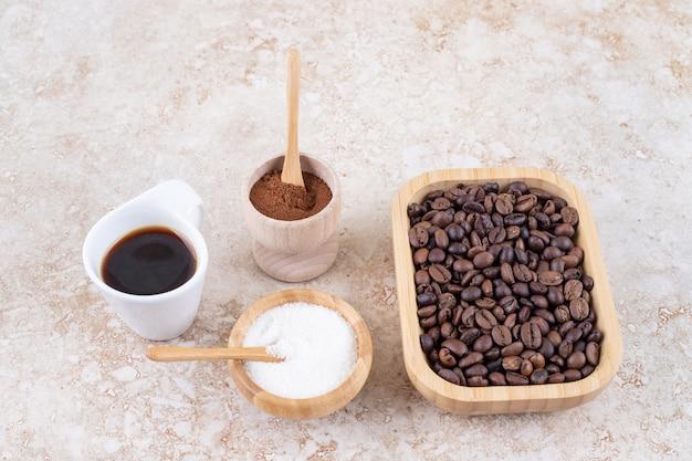 Een arrangement van koffiekopje, suiker, gemalen koffiepoeder en een stapel koffiebonen in een houten schotel